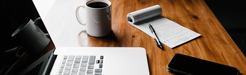 Table en bois avec un ordinateur portable, un téléphone mobile, un bloc note, un stylo et une tasse de café. Outils pour contacter BAN
