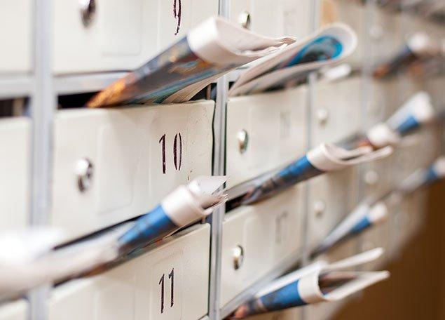 groupe de boites aux lettres contenant plusieurs journaux et matériel publicitaire
