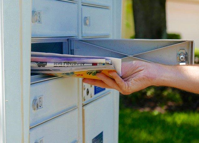 main d'une personne retirant une pile de courrier, journaux et matériel marketing d'une boite aux lettres ouverte
