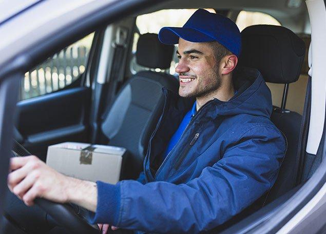 homme souriant assis au volant d'un pick up avec habits de livreur ou porteur et colis sur le siège co-pilote