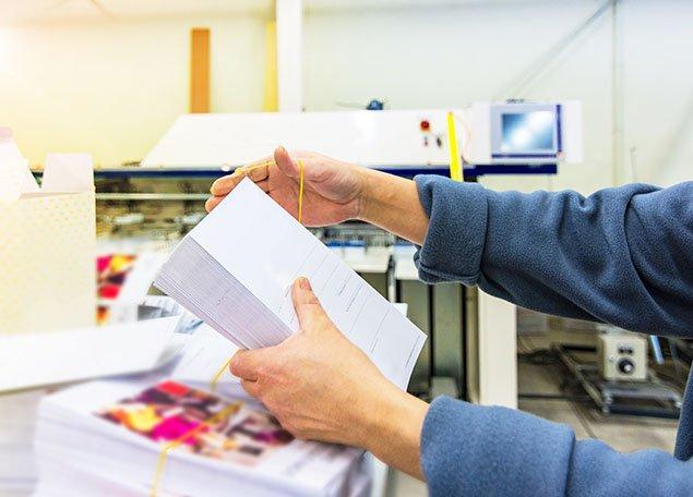 mains d'homme mettant sous pli un paquet d'enveloppes et flyer