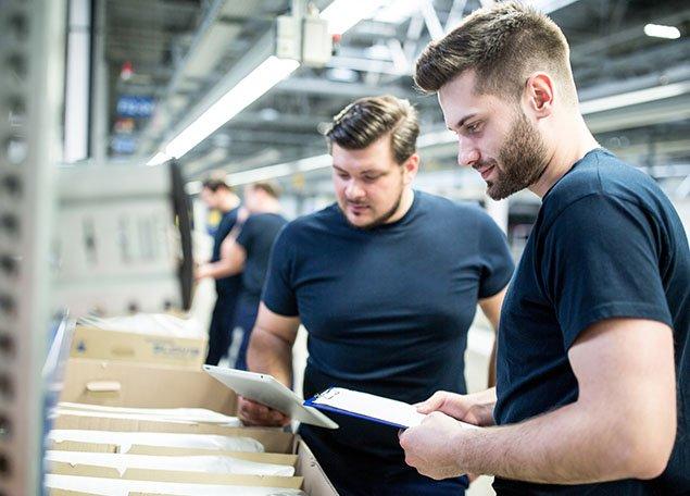 deux homme dans un entrepôt de logistique debout face à une boite pleine de document et courrier