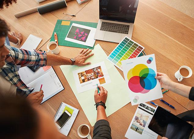 vue de haut d'un groupe de personnes travaillant sur un projet de graphisme, sur la table se trouvent un ordinateur, des palettes de couleurs, des maquettes de flyers, un agenda, un téléphone et des tasses de café
